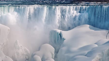 véu : Winter at Niagara Falls. The flow of water falls on blocks of ice and snow Vídeos