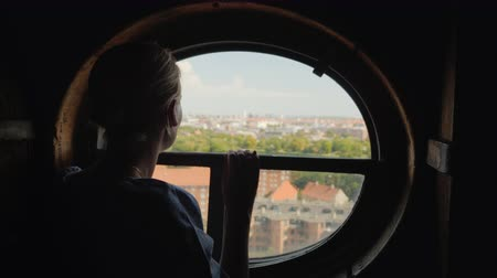 danimarka : Silhouette of a woman looking in a round window on the rooftops of the city of Copenhagen in Denmark Stok Video