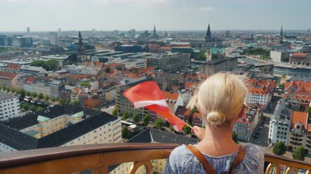 parafusos : A woman with the flag of Denmark in her hand wipes out on to Copenhagen city, stands on the ancient tower with a spiral staircase. before her you can see the whole city