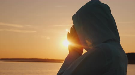 clasped : A middle-aged woman in a hood praying near the lake at sunset Stock Footage