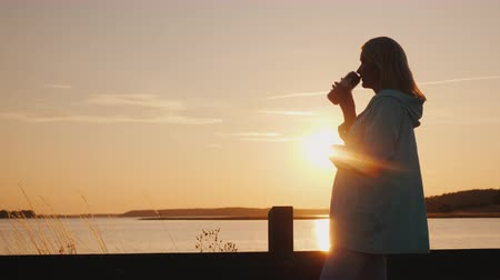 алкоголизм : A middle-aged woman is drinking beer by the lake at sunset. Стоковые видеозаписи