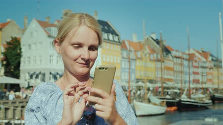 danimarka : A happy woman uses a smartphone, stands on the background of the canal and the popular tourist street of Copenhagen
