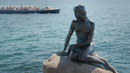 Скандинавия : Monument to a little mermaid in the harbor of Copenhagen. In the background you can see a sightseeing boat with tourists