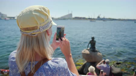 copenhagen : The tourist photographs the famous statue of the Little Mermaid in the harbor of Copenhagen, Denmark