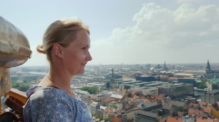 climbed : The woman admires the view from a height to Copenhagen. It stands on top of the Church of the Savior, where she climbed the famous spiral staircase Stock Footage