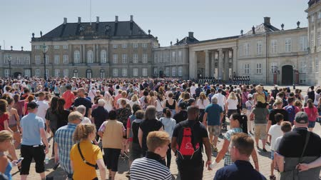 copenhagen : Copenhagen, Denmark, July 2018: A crowd of people running to take pictures and look at the changing of the guard at the royal palace in Copenhagen Stock Footage
