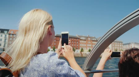danimarka : A woman takes pictures of Copenhagens sights, sails on the excursion ship through the citys canals