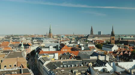 copenhagen : The city of Copenhagen, an old city often with old-tiled roofs and spiers. Pan shot