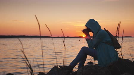 clasped : A lonely woman sits on a rock near a picturesque lake at sunset