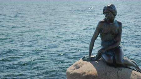 danimarka : Copenhagen, Denmark, July 2018: The famous staunch of the Little Mermaid in the harbor of Copenhagen. One of the characters of Hans Christian Andersons fairy tale is a symbol of the city Stok Video