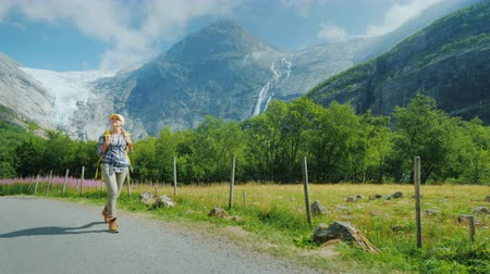 vários : An active successful woman travels through Norway, walks against the backdrop of mountains with a backpack