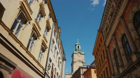 stockholm : Steadicam shot of St Nicholas - Storkyrkan bell tower in Stockholm. View through a narrow street with old houses Stock Footage