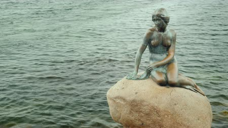 copenhagen : Copenhagen, Denmark, July 2018: Copenhagens famous landmark - the Little Mermaid statue on a rainy cloudy day
