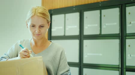 paket : A woman writes the address on the parcel, stands in the post office on the background of mailboxes Stok Video