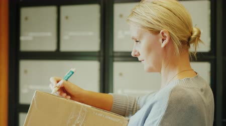 sending : A woman writes an address on the parcel box in the post office Stock Footage