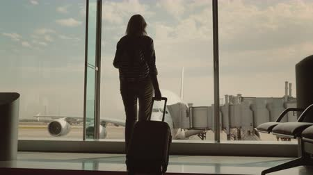 pas : A woman with luggage goes to a large window in the airport terminal. Outside the window you can see a beautiful airliner. In anticipation of the journey
