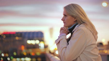 zábradlí : A young woman stands leaning on the railing of the bridge, admiring the beautiful sunset. Dostupné videozáznamy