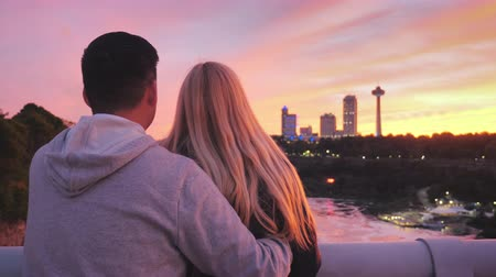 hayran olmak : Multi-ethnic couple standing on a bridge between the USA and Canada, admiring a beautiful sunset