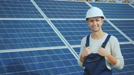 solarium : Portrait of a worker in a helmet, looking at the camera, stands against the background of a row of solar panels. alternative energy
