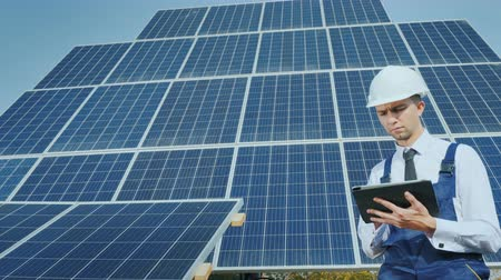 tuning : A young businessman in a white helmet uses a tablet on the background of solar panels