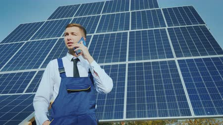ladění : Young engineer speaks on the phone on the background of large solar panels