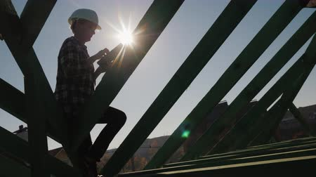 work at height : Silhouette of an engineer, works among the rafters of the roof, uses a tablet. Technical control in construction Stock Footage