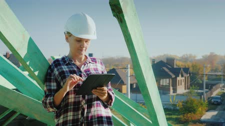 жесткий : A female architect is working with a tablet on the roof of a house. Technical and authors control in construction Стоковые видеозаписи