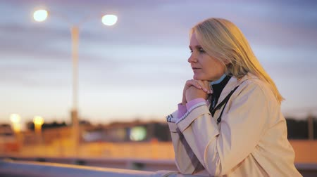 hayran olmak : A middle-aged woman stands on a bridge at the railing and looks thoughtfully into the distance in a night city Stok Video