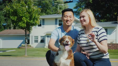 shepherds house : Happy multi-ethnic family with a dog, against the background of a new home. Holds the key in his hand Stock Footage