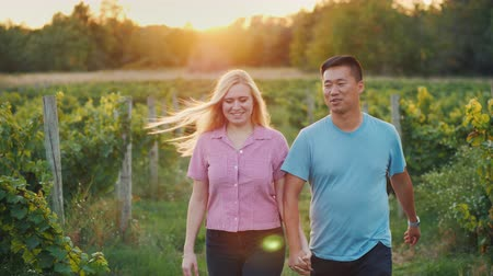 parreira : Happy multiethnic couple walking in the vineyard. Wine tasting and tourism concept