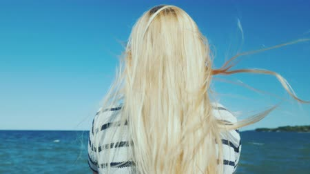 see off : Blonde woman with long hair looks at the sea. Wind ruffles her hair