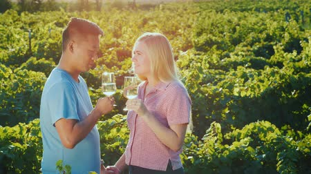 şarap kadehi : Young multi-ethnic couple tasting red wine at the winery. Private tasting and tourism concept