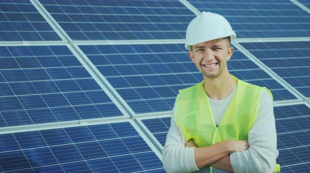 ladění : Portrait of a worker in overalls and a helmet on the background of solar panels. Smiles, looks into the camera Dostupné videozáznamy
