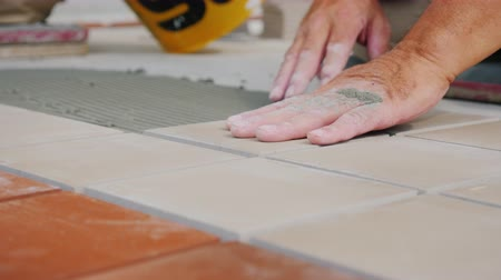 склеивание : Workers laying tile on the floor, close-up