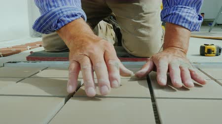 склеивание : A man is laying tiles on the floor, only hands are visible in the frame