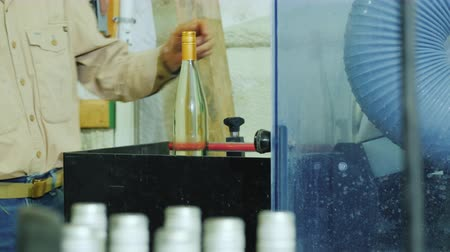 row : A worker picks up wine bottles from a conveyor belt, working in a small winery Stock Footage