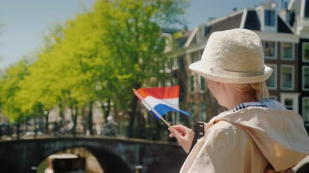 arka görünüm : Young stylish woman with the flag of the Netherlands stands on the canal on the background of ancient buildings. Tourism in the Netherlands