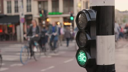 estreito : Many bicycles ride on Amsterdam street, in the foreground a special traffic light for cyclists. Environmentally friendly mode of transport Stock Footage