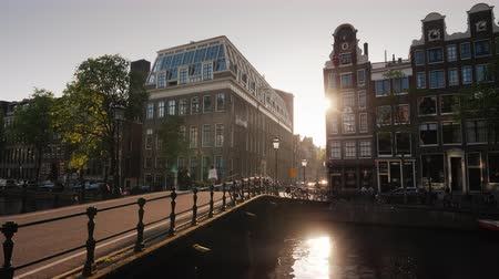 pedestres : A beautiful sunset in Amsterdam, the sun shines through the houses and is reflected in the water of the canal