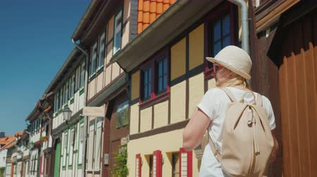 hayran olmak : A woman walks along the picturesque street of a small German town, admiring the beautiful old architecture of the houses. Tourism in Germany and Europe concept