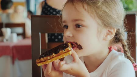 pigtailler : The portrait of a little girl with two pigtails, which eats a chocolate waffle, all smeared with sweets