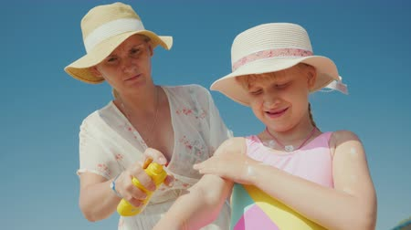 щит : Mom puts sunscreen on the skin of her daughter. Rest and sun protection