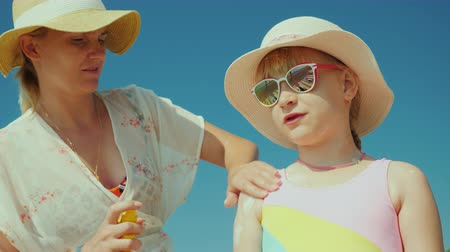уход за телом : A caring mother applies sunscreen to her daughters skin. Solar radiation protection and safe tan