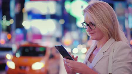 vezes : Business woman uses a smartphone on busy Times Square in New York. The famous yellow cabs are passing by - the symbol of the city.