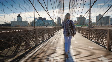 sabah : Carefree tourist walks along the Brooklyn Bridge towards Brooklyn. Morning in New York Stok Video