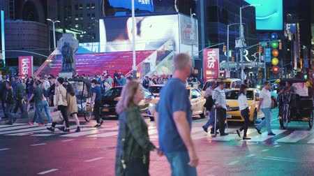 kereszt : New York, USA, October 2018: A crowd of pedestrians crossing the street in Times Square. Advertising lights highlight the street
