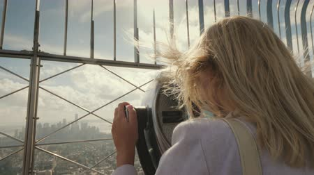 sight seeing : A woman looks at a beautiful view of New York from the observation deck. The wind plays with her hair. Visit New York concept