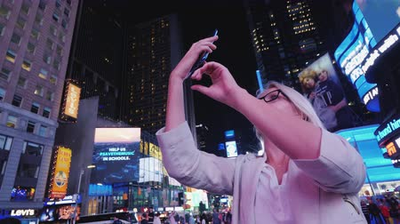 times : New York, USA, October 2018: Woman tourist takes pictures on Times Square in New York. Tourism and travel in the USA Stock Footage