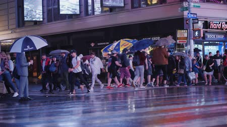 vezes : New York, USA, October 2018: A crowd of pedestrians with umbrellas in their hands in a hurry to cross the street in a busy area of Manhattan