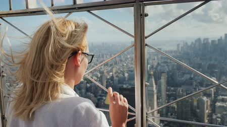gözlem : A woman looks down at a beautiful view of the business district of Manhattan. It stands at the fence of the observation platform of a skyscraper Stok Video